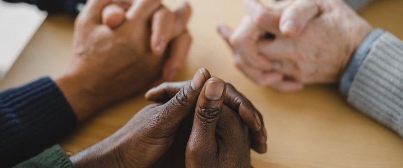 Group of multiethnic people at a table with open bibles, praying
